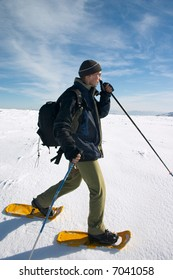 tourist in snow-shoes traveling in winter mountains