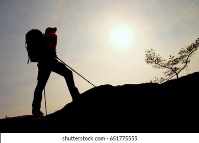 Tourist with sporty backpack and poles in hands stand on rock  watching up to hill for next step. Sunny spring daybreak in mountains. Vivid and strong vignetting effect..