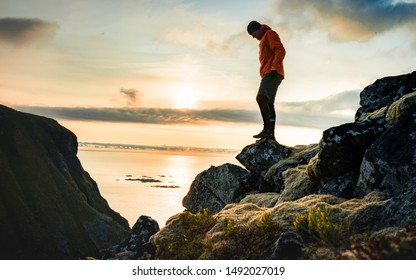 Tourist stand alone on a rock and watching sea horizon within sunset. Rocky part of path with view into distance.