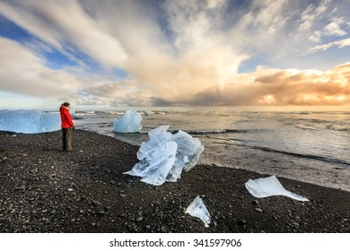 Tourist standing among ice pieces on a beach in southern Iceland