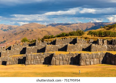 Tourist standing in front of the giant granite stone blocks of the Sacsayhuaman Inca ruin located in the Andes Mountain Range around the ancient Inca capital city of Cusco, Peru.