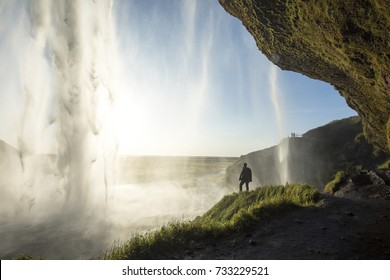 Tourist standing in front of Seljalandsfoss one of the best known waterfalls in southern Iceland, The most famoust Icelandic waterfall , beautiful amazing landscape from Iceland,
