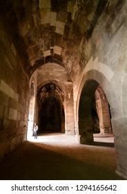 Tourist standing under stone arches of Sultanhani Caravanserai enclosed storage and winter accomodation area Turkey