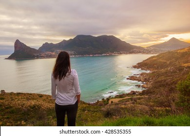 A tourist stands at a lookout point enjoying a beautiful view of Hout Bay