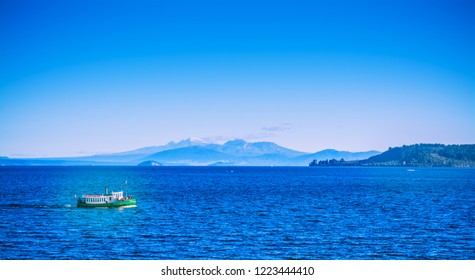Tourist steamboat crossing the deep blue waters of lake Taupo with Ruapehu mountains in the background on a beautiful sunny day. North Island Volcanic Plateau, New Zealand
