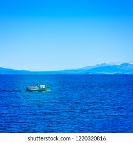 Tourist steamboat in the deep blur waters of Taupo lake with Ruapehu mountains in the background on a beautiful sunny day. North Island Volcanic Plateau, New Zealand