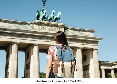 A tourist or a student with a backpack near the Brandenburg Gate in Berlin in Germany, looks at the sights.