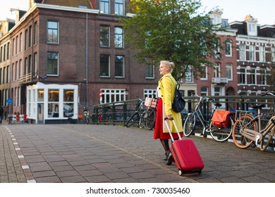 The tourist with suitcase is walking in the street of Amsterdam city in autumn