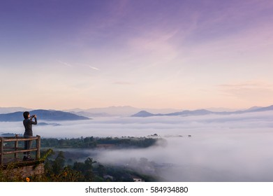 Tourist with Sunrise and sea of clouds over Pai District Mae Hong Son, THAILAND. View from Yun Lai Viewpoint is located about 5 km to the West of Pai town centre above the Chinese Village.