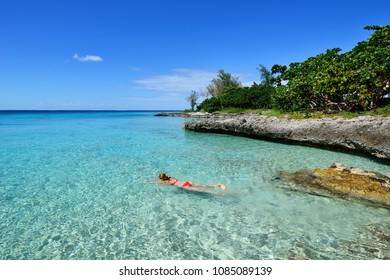 Tourist swimming in turquoise waters of the Caribbean sea on the wild noon coast of Cuba
