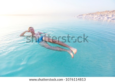Tourist swims in turquoise water of the Dead Sea. Jordan landscape