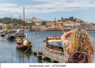 A tourist takes a photo of the famous rabelos boats in the city of Oporto. The rabelo boat is a Portuguese boat, typical of the Douro River. Portugal