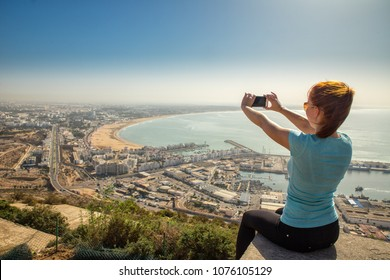 the tourist takes a picture of the agadir with a smartphone from the viewpoint