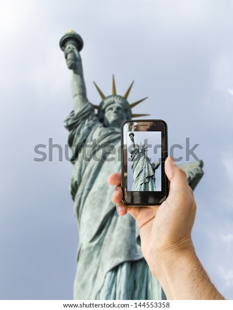 tourist takes a picture with his mobile of statue of liberty in new york
