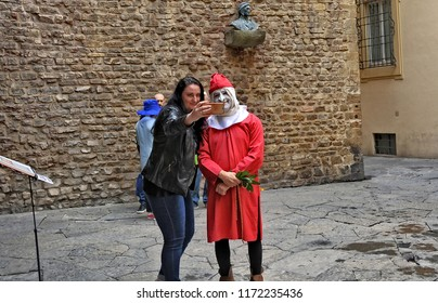Tourist takes selfie with an actor, who is going to perform as Dante Alighieri, reading Divine Comedy near Dante's museum. History and Art of Italy. Italy, Florence – April 17, 2018