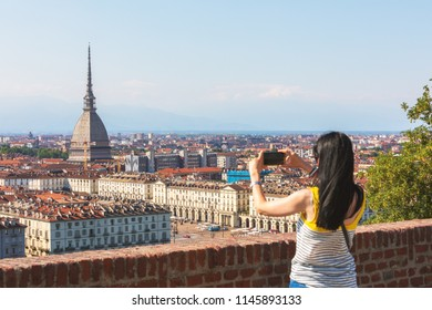 Tourist taking a panoramic photo of Torino (Turin, Italy) city center with landmark of Mole Antonelliana towering over the city. Woman using smartphone to photograph.