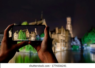 Tourist taking photo of canal of Bruges, tower and historic buildings at night, Bruges, Belgium. Man holding phone and taking picture.
