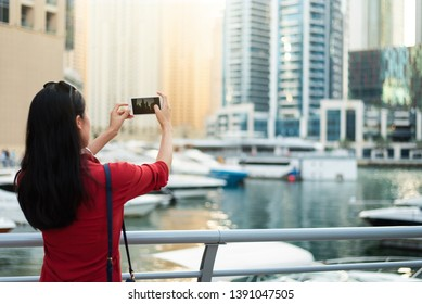 Tourist taking a photo of Dubai marina with a smart phone