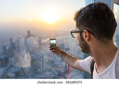 Tourist taking a photo of the Dubai skyline from above.