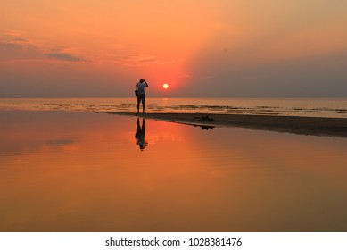 Tourist taking a photo of a lovely orange sunset over the quiet waters of the Baltic sea in Jurmala, Latvia.