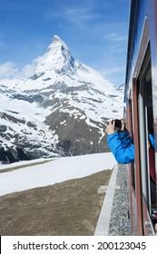 Tourist taking photo of Mountain Matterhorn from the train in Switzerland