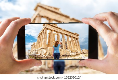 Tourist taking photo of young woman in Athens by cell phone, Greece. This place is a top landmark of Athens. Picture of the Ancient Greek Parthenon on smartphone. Traveling and vacation concept.