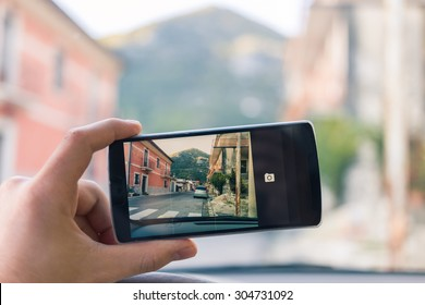 A tourist is taking a photograph, with his smartphone, of a countryside road in a little european village