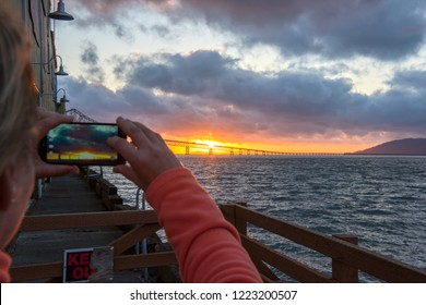 Tourist taking picture of Astoria-Merger bridge in the lights of sunset at Astoria, Oregon, USA
