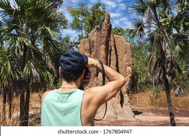 Tourist taking a picture of a big magnetic termite mound. Fit man holding camera,   wearing cap and t-shirt. Strong arms. Litchfield national park, Northern Territory NT, Australia