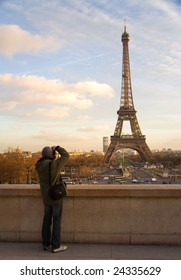 A tourist taking picture of the Eiffel Tower with the European Union symbol on it