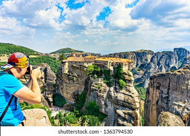 Tourist taking a picture Holy Monastery of Varlaam - one of Eastern Orthodox monasteries located in rock formation Meteora. Greece.Europe.
