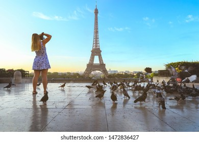 Tourist taking picture on Eiffel tower in Paris with pigeons flying around, France