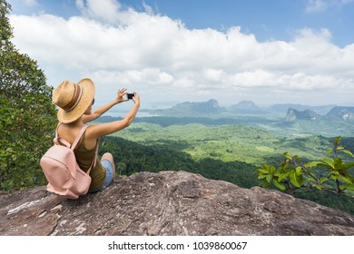 Tourist taking picture on her smartphone from top of mountain. Woamn in hat and with backpack sitting on rock. Travel concept.