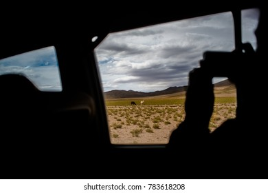 Tourist taking a picture with phone from 4x4 car window near Salvador Dali Desert during dessert crossing in Uyuni Salt Flats in Bolivia.