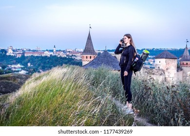 Tourist taking picture from view point. Girl with backpack, camers and hat. Travel concept.