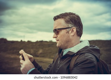 a tourist taking pictures of Hadleigh Park (Essex, UK) with his smartphone