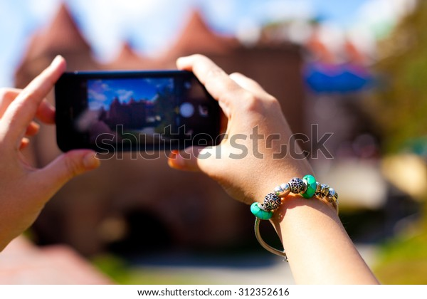 Tourist taking pictures on her phone. Hands with beautiful bracelet holding phone