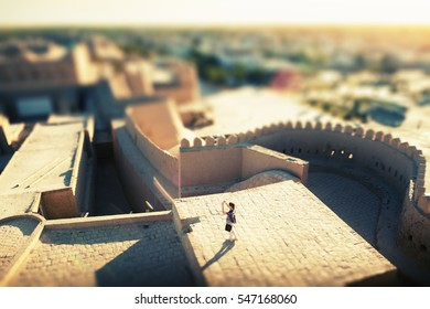 Tourist taking pictures on the roof of building in ancient city of Itchan Kala at sunny day, Khiva, Uzbekistan