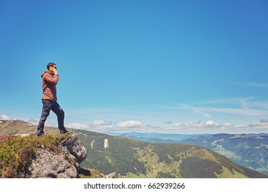 Tourist a taking selfie on peak above mountain valley with sunrise and fog, moon background