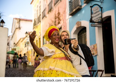 "Tourist taking selfie photos with Brazilian women ""Baiana"" in Pelourinho, Salvador, Bahia, Brazil"