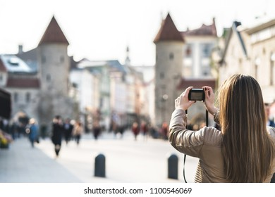 Tourist in Tallinn taking photo of Viru Gate. Woman on vacation taking picture of landmark in Estonia. People walking in popular street. Back view of girl with camera.