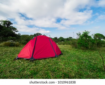tourist tent camping on green grass and sky