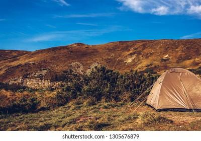 Tourist tent in Carpathian mountains under blue sky.Travel destination for active tourism in Europe.Instagram vintage film filter. Go hiking in Carpathians in autumn season