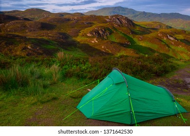 Tourist tent at the foot of the hill. Camping on the grass in Scotland. Scottish landscape at the Golden hour. Green tent in summer mountains. Amazing evening highland.