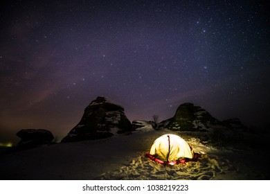 Tourist tent in the night with the starry sky over the Urals