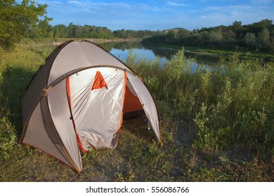 Tourist tent on the banks of the river in summer