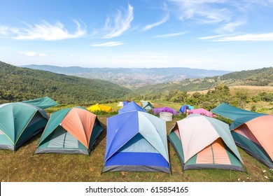 Tourist tents in camp among meadow on the mountain.
