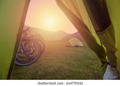 Tourist tents in the camp stand in the valley of a clean river, surrounded by high mountains, hills. Group of cyclists traveling along mountain roads of Tien Shan, Kyrgyzstan, Asia. Sunset, sunlight.