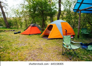 Tourist tents in forest at campsite. Camping tent on nature in summer. Travel background. Place for picnic outdoors.