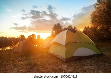 tourist tents at riverbank in forest in summer morning